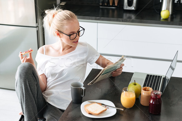 Serious focused lady reading newspaper while have breakfast Stock photo © deandrobot