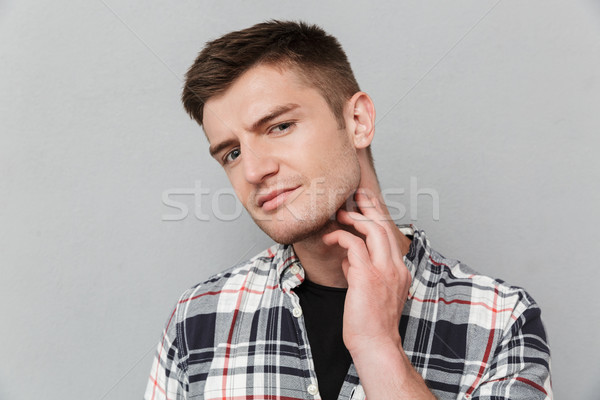 Portrait of a concerned young man in plaid shirt Stock photo © deandrobot