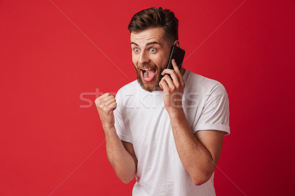 Handsome young surprised man talking by mobile phone make winner gesture. Stock photo © deandrobot
