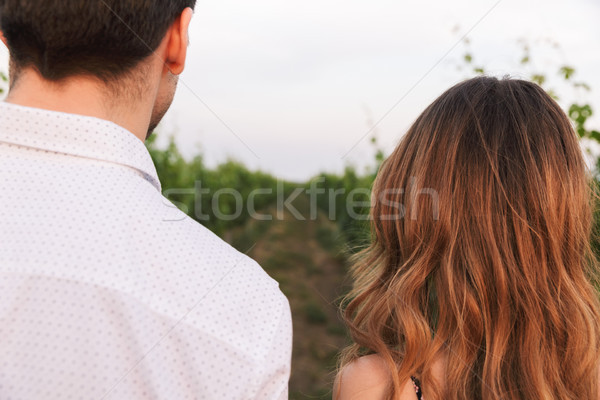 Photo from back closeup of young couple man and woman, walking t Stock photo © deandrobot