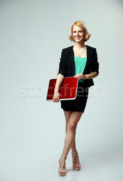 Full length portrait of a happy woman standing with laptop on gray background Stock photo © deandrobot