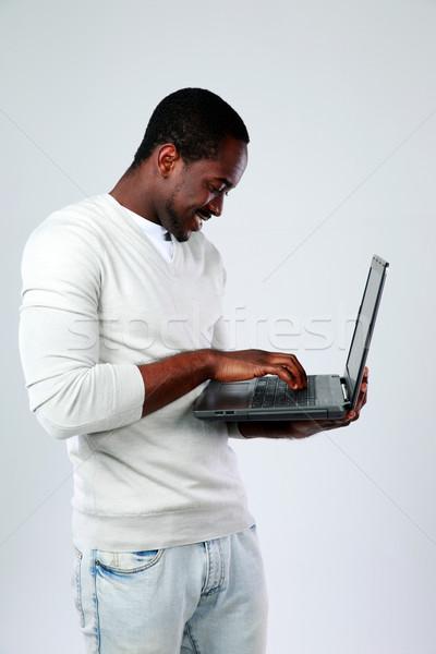 Afrikai férfi laptopot használ áll felfelé szürke Stock fotó © deandrobot