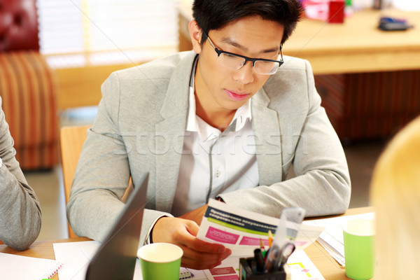 Asian businessman in glasses sitting at the table and reading instruction in office Stock photo © deandrobot