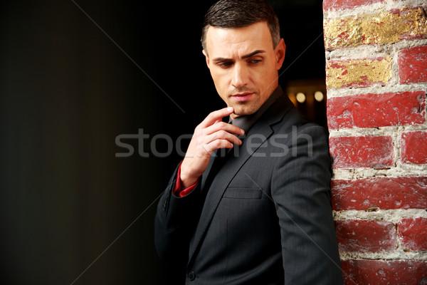 Portrait of a pensive businessman standing near brick wall Stock photo © deandrobot