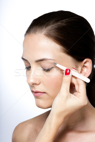 Attractive young woman plucking eyebrows Stock photo © deandrobot