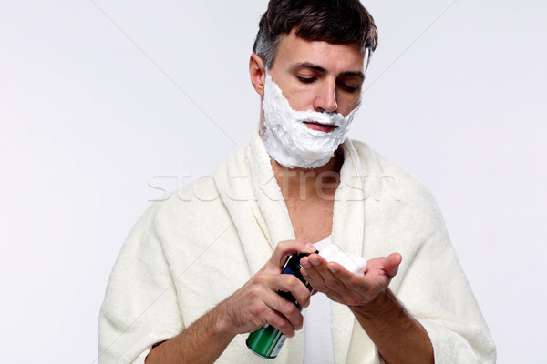 Man with shaving cream over gray background Stock photo © deandrobot