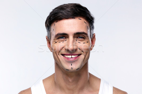 Smiling man marked with lines for plastic surgery Stock photo © deandrobot