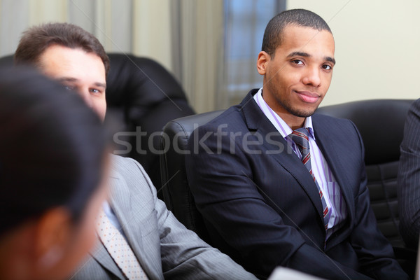 Multi ethnic business team at a meeting. Focus on african-american young man Stock photo © deandrobot