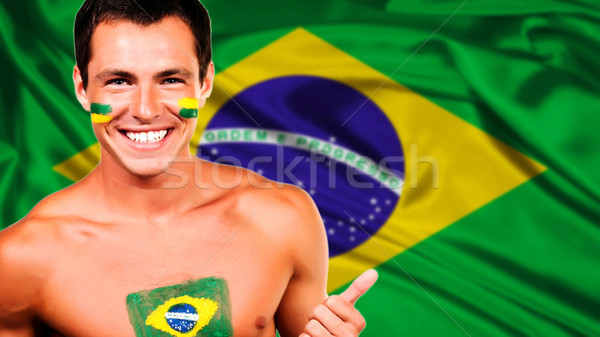 Happy brazilian fan celebrating over brazil flag background Stock photo © deandrobot
