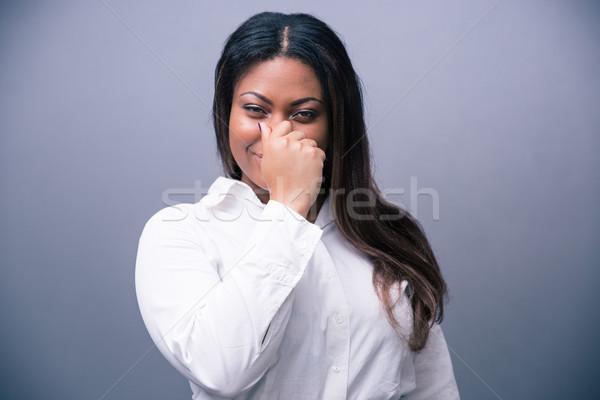 Afrikaanse zakenvrouw neus grijs naar camera Stockfoto © deandrobot