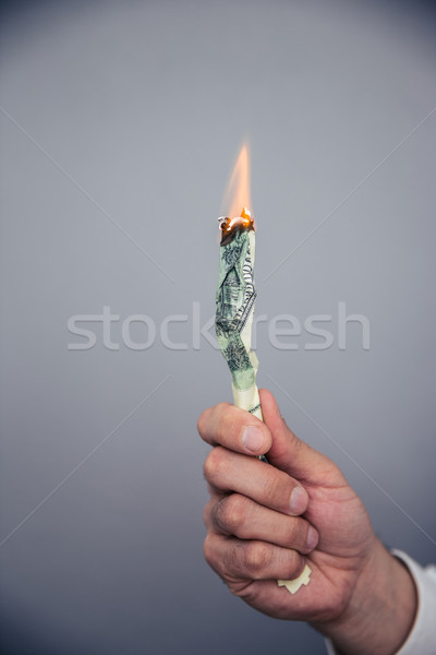 Male hand holding a burning US dollar bill  Stock photo © deandrobot
