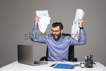 Businessman sitting at the table with crumpled paper Stock photo © deandrobot