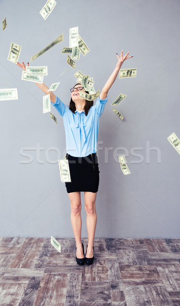 Stock photo: Business woman standing in the rain of the dollar bills
