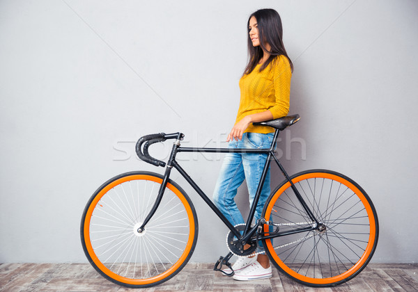 Smiling woman standing near bicycle Stock photo © deandrobot