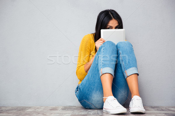 Woman covering her face with tablet computer  Stock photo © deandrobot