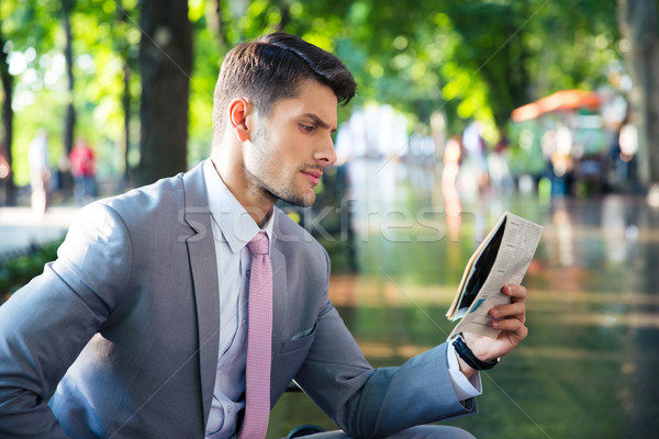 Stock photo: Businessman reading newspaper outdoors