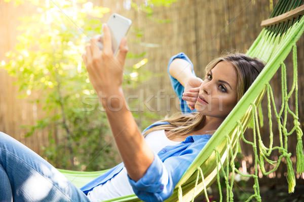 Vrouw foto smartphone buitenshuis meisje Stockfoto © deandrobot
