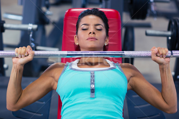 Woman lifting barbell on the bench Stock photo © deandrobot