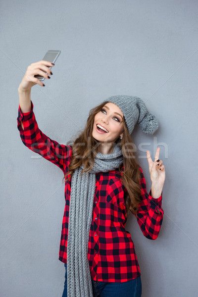 Woman making selfie photo and showing peace sign Stock photo © deandrobot