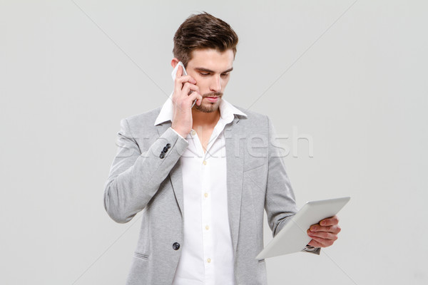 Young businessman talking on cellphone and using tablet Stock photo © deandrobot