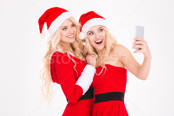 Cheerful blonde sisters twins making selfie using cell phone Stock photo © deandrobot