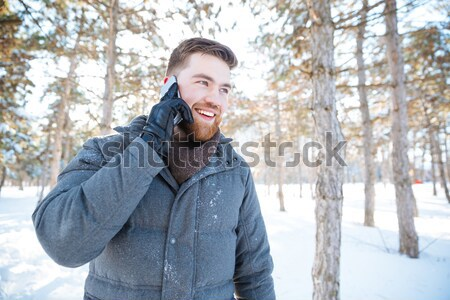 Smiling man talking on the phone in winter park Stock photo © deandrobot