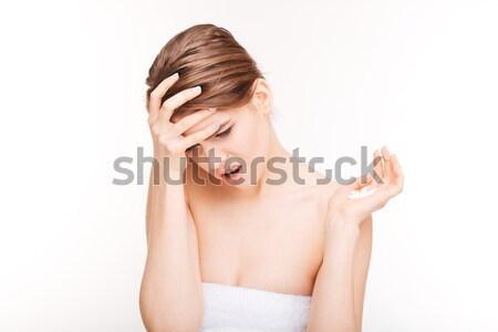 Woman with headache holding pills Stock photo © deandrobot