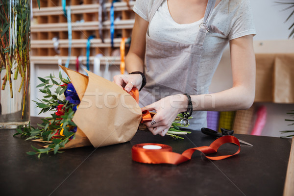 Hands of woman florist making flower bouquet in shop Stock photo © deandrobot