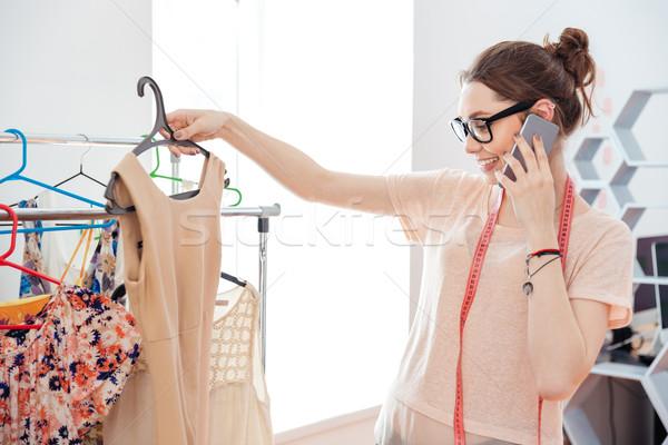 Woman fashion designer choosing dress and talking on mobile phone Stock photo © deandrobot