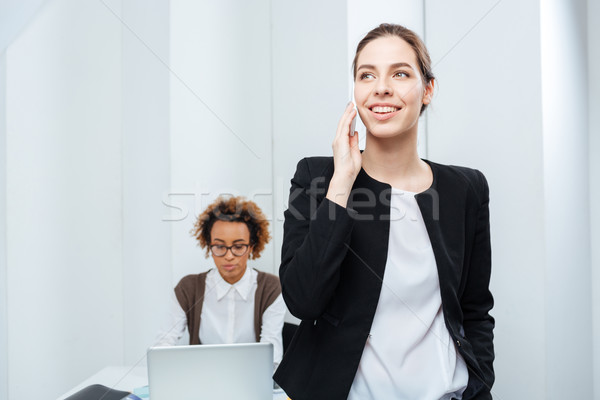 Businesswoman talking on phone while her colleague working with laptop Stock photo © deandrobot