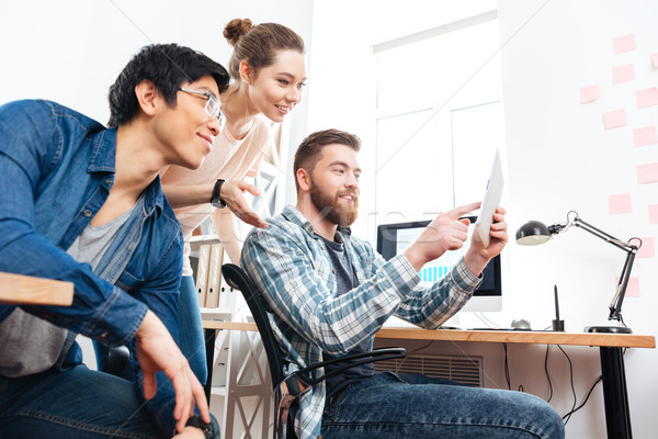 Three  businesspeople working and using tablet in office Stock photo © deandrobot