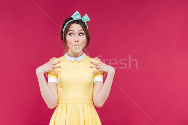 Cute playful pinup girl doing bubble with chewing gum Stock photo © deandrobot