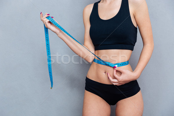 Woman measuring her waist with centimeter tape on grey background Stock photo © deandrobot