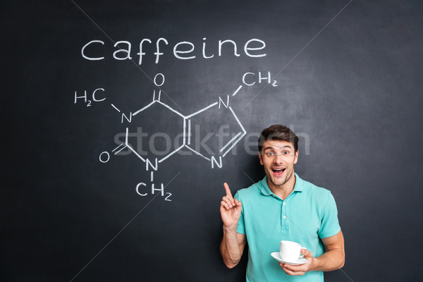 Smiling young man pointing on drawn caffeine molecule chemical structure Stock photo © deandrobot