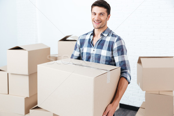 Smiling happy man carrying carton boxes at new flat Stock photo © deandrobot