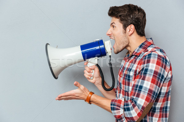 Side view portrait of a casual man yelling into megaphone Stock photo © deandrobot