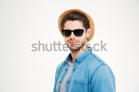 Confident young man in sunglasses and hat Stock photo © deandrobot