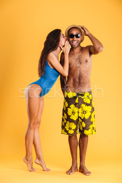 Pretty girl in swimsuit telling someting to her african boyfriend Stock photo © deandrobot