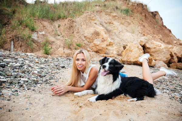 Smiling young woman lying with her dog on the beach Stock photo © deandrobot