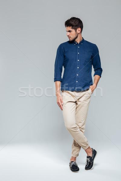 Teljes alakos portré férfi áll lábak keresztbe lezser Stock fotó © deandrobot