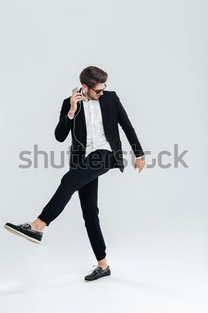 Businessman in black suit listening music with earphones and dancing Stock photo © deandrobot