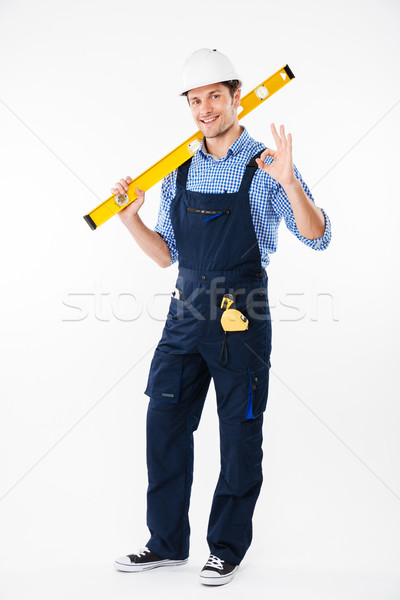 Portrait of a smiling builder standing and showing okay gesture Stock photo © deandrobot