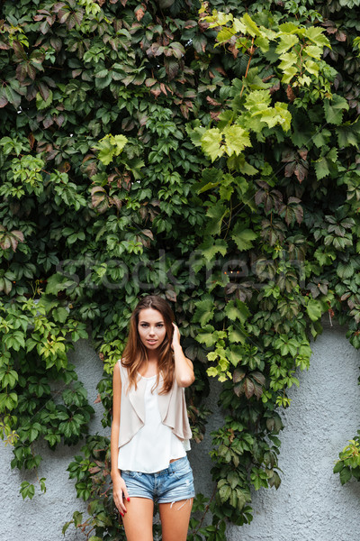 Young cheerful girl posing outdoors with green leaves background Stock photo © deandrobot