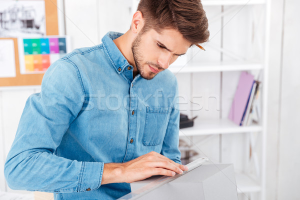 Concentrated young man measuring box with ruller at the office Stock photo © deandrobot