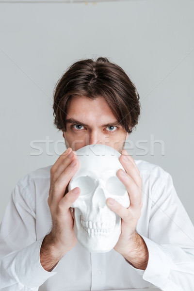 Man holding fake skull at his face Stock photo © deandrobot