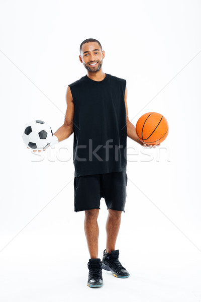 Happy african sports man holding basketball and soccer ball Stock photo © deandrobot