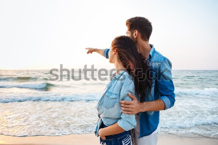 Couple standing and pointing away on the beach Stock photo © deandrobot