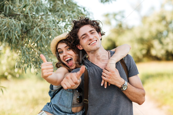 Stock photo: Young happy cheerful couple showing thumbs up and hugging