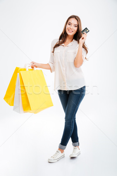 Happy young woman holding shopping bags and bank card Stock photo © deandrobot