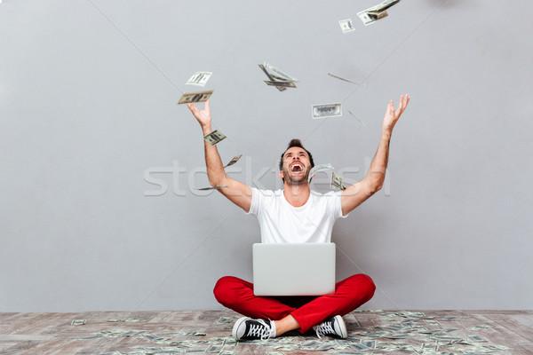 Casual hombre sesión piso lluvia dinero Foto stock © deandrobot
